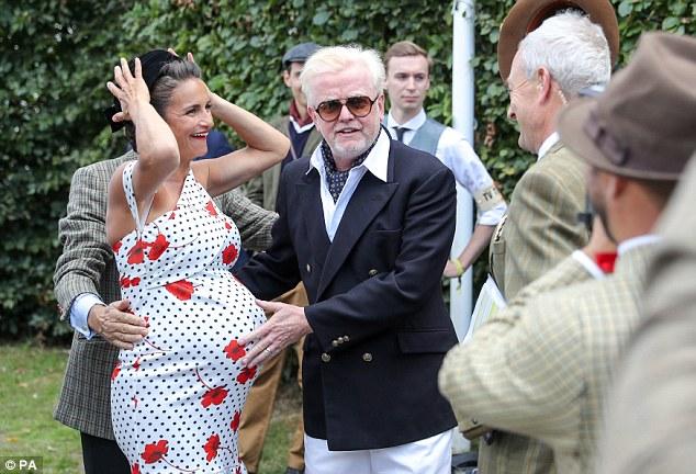 Excitation: Natasha, qui doit donner naissance à des jumeaux en quelques semaines, a présenté sa grosse bosse de bébé dans une élégante robe blanche à une épaule ornée de pois et de coquelicots