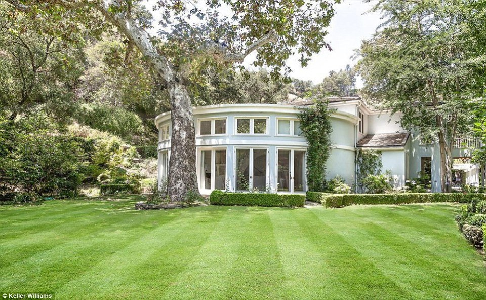 The 2.7 acres of grounds feature a manicured lawn, hedgerows, and several large trees which dapple the grass with shade