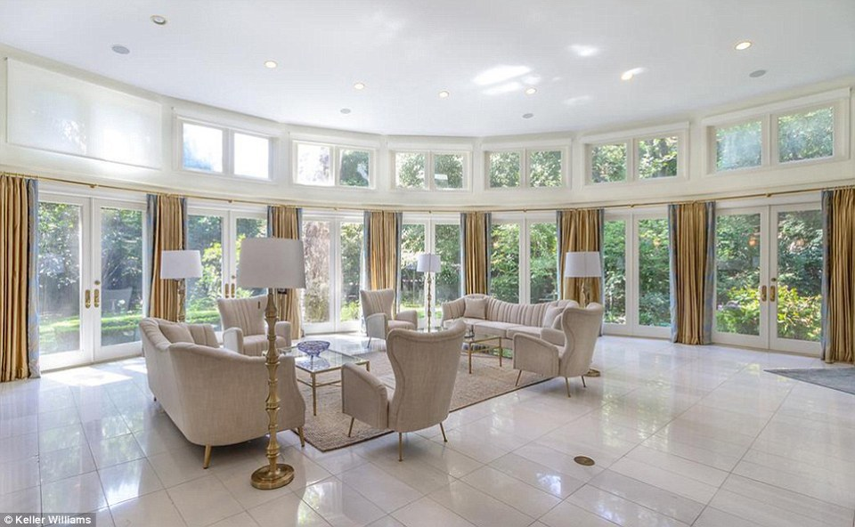 The home features a spectacular circular living-room with marble floors which looks out over almost three acres of manicured gardens and boxwood walkways