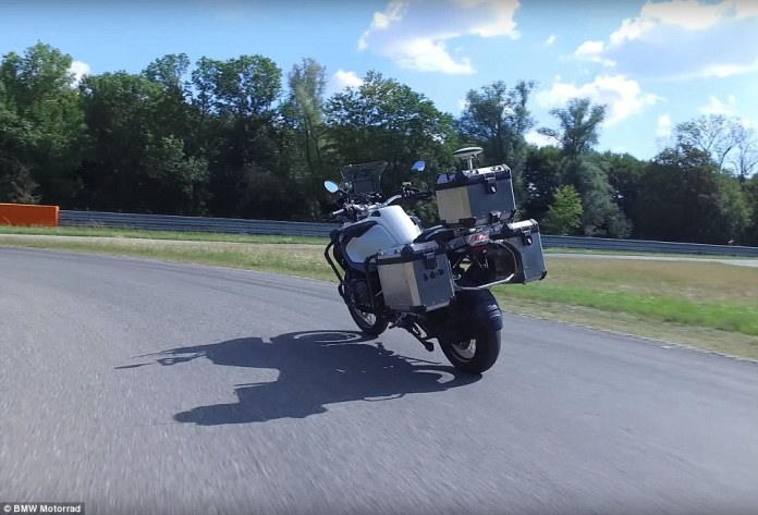 BMW has revealed a self-driving motorcycle that can speed around a racetrack and even park itself without behind the handlebars. Pictured is the vehicle driving itself around a BMW test track