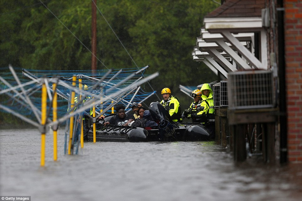 Firefighters use a boat to rescue three people from their flooded home during Hurricane Florence in New Bern