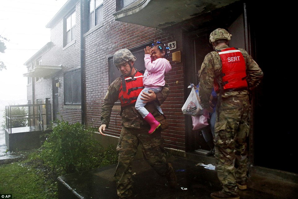 A rescue team from the North Carolina National Guard 1/120th battalion evacuates a family as the rising floodwaters from Hurricane Florence threatens their home in New Bern on Friday
