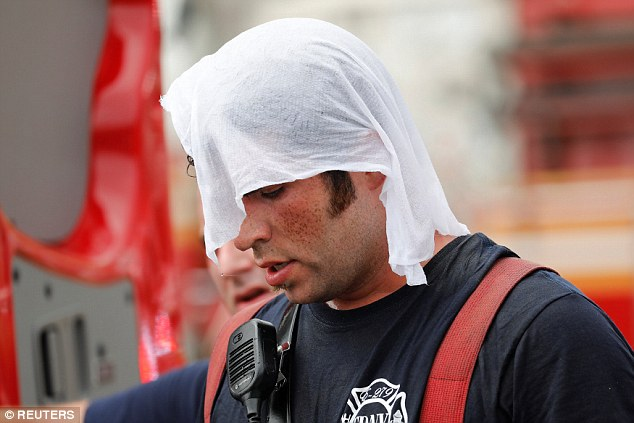 A FDNY firefighter cools off after working a seven-alarm fire at the Kings Plaza Shoppin