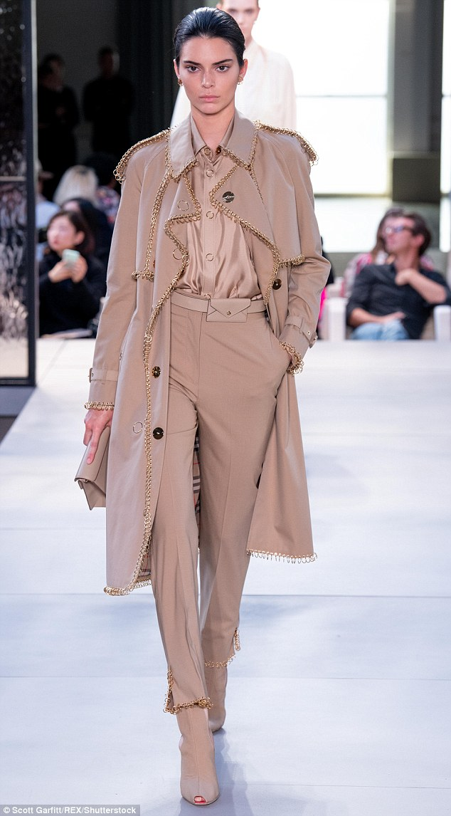 Look: Kendall took the catwalk in an all-beige outfit including a trench embellished with chains — a modern take on Burberry's classic design