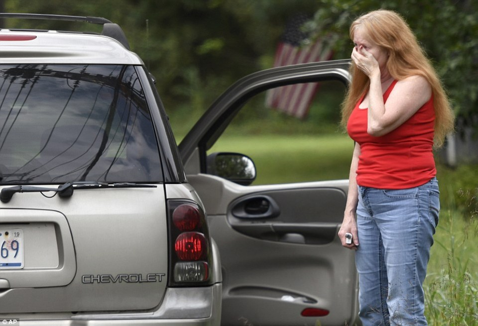 A woman reacts at the scene of the shooting on Thursday morning as police work nearby. Three people were killed and three others were injured by the female shooter identified as Moseley, according to officials