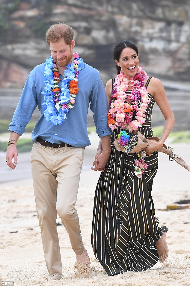 The royal couple pictured with garlands of flowers, or 'leis', dangling around their necks as they walk through the sand