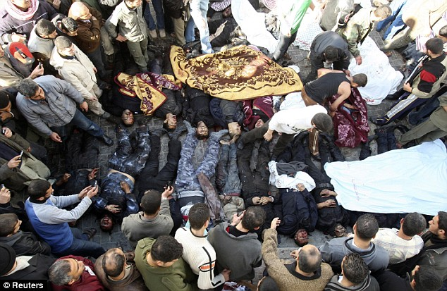 Mourners watch over the bodies of Palestinians at Shifa hospital in Gaza City