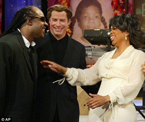 Oprah Winfrey, pictured during her 50th birthday celebrations, is flying to see Travolta (centre)
