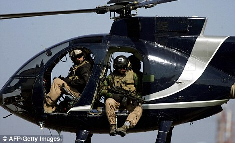 Heavily-armed members of the Blackwater fly over Baghdad on a mission (pic credit - dailymail.co.uk)