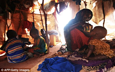 Desperation: A woman feeds her child at a newly formed camp for refugees affected by drought in Somalia yesterday. Somalis are also contending with hardline Islamists seeking to impose a strict form of Sharia law on the country