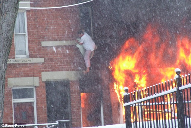 The moment terrified house fire victim leaps 10ft from flames into snow below  Daily Mail Online