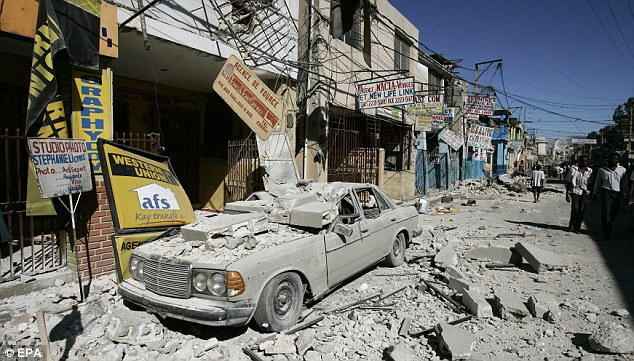 Buildings were destroyed in the devastating quake. Here, a car is seen covered in rubble in downtown Haiti