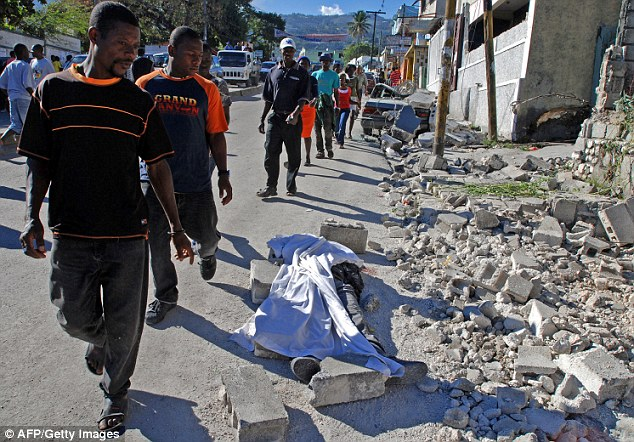 Haitians pass a covered body as they take in the devastation in Port-au-Prince