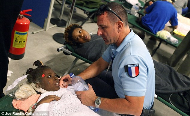 An injured girl is given water by a French aid worker at a makeshift field hospital in Port-au-Prince