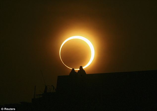 A Chinese couple watches the solar eclipse over Zhengzhou, in the country's central Henan province