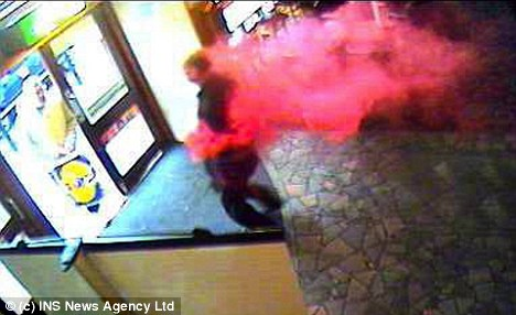 Armed bank robber enveloped by hot pink smoke as security dye explodes following cash raid