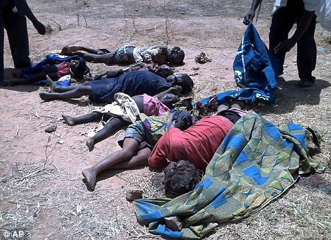 No mercy: Victims of the violence lay on the dusty ground in Jos, Nigeria after rioters armed with machetes slaughtered more than 500 people overnight