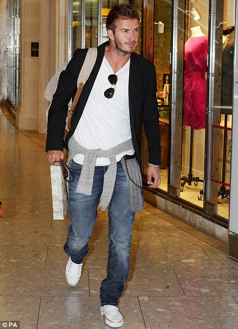Retail therapy: David Beckham does some duty free shopping at Heathrow today before boarding a flight to Los Angeles