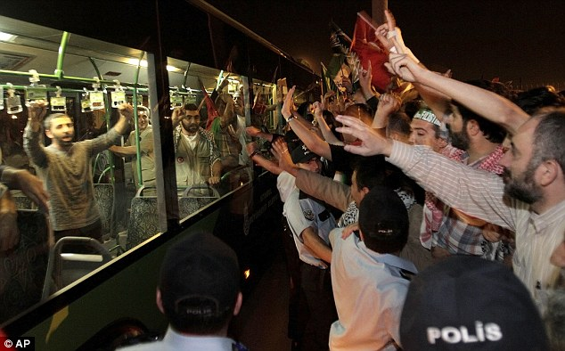 Heroes' welcome: Demonstrators greet Turkish activists at the airport in Istanbul, Turkey, today