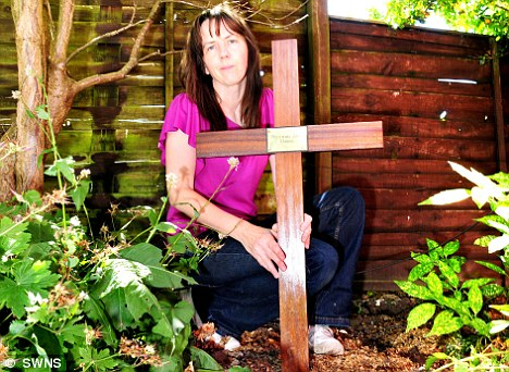 Dangerous: Liz Maggs with the cross that was removed by council officials