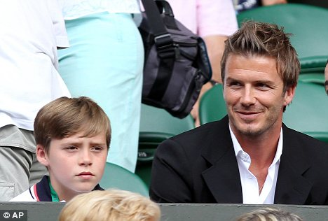 England footballer David Beckham, right, sits with his son Brooklyn, left, as he arrives on Centre Court at the All England Lawn Tennis