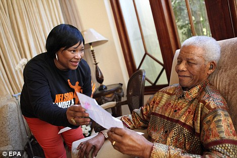 Victim: Nelson Mandela's daughter Zindzi Mandela was attacked hours after this photo was taken showing her frail father a letter at his 92nd birthday party