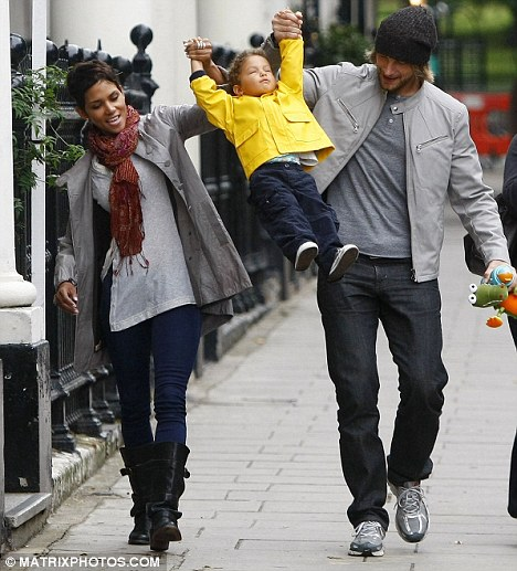 Up she goes: Actress Halle Berry and her former boyfriend Gabriel Aubry take their daughter Nahla for a walk in London