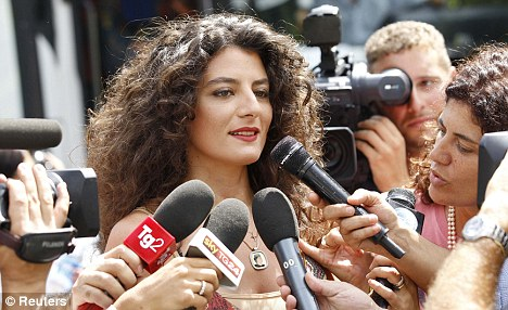 Glamorous: A woman speaks to the media as she arrives for the  conversion party at the Libyan Academy in Rome