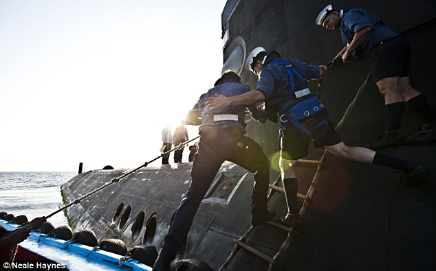 An officer is welcomed aboard on the HMS Talent as the submarine heads into Suez