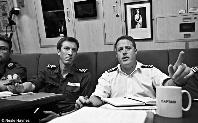 Commander Asquith (on right) and Lieutenant Commander Bull in the wardroom on HMS Talent under a portrait of the Queen