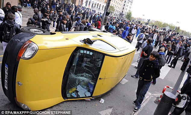 High school students damage a car during a demonstration in Lyon, France