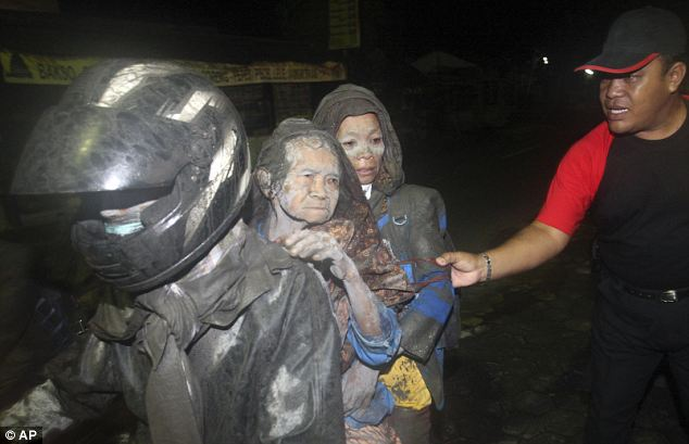 Ghostly faces: Two women covered in dust arrive to safety on the back of a motorbike