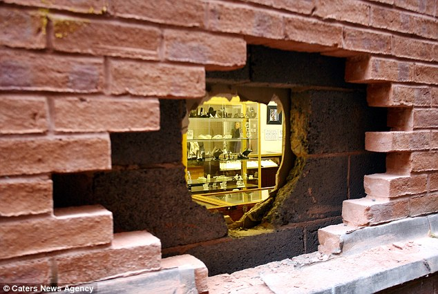 A thief painstakingly spent more than three hours removing outside bricks then smashing his way through an interior wall before carrying out the heist.