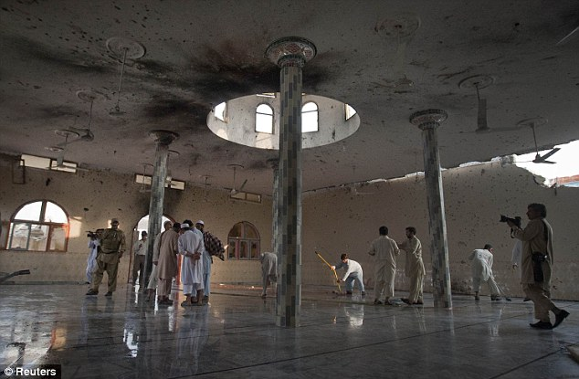 Blast: Worshippers and soldiers inside the main hall of the Waali mosque. Scorch marks are visible on the ceiling