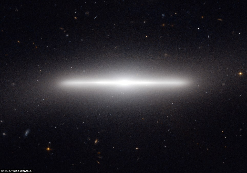 This astonishing shot shows a distant galaxy seen from side-on so it looks like a thin strip of light