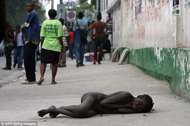 Horror: A woman lies on the pavement near the General Hospital, in Port-au-Prince where people infected by cholera are being treated