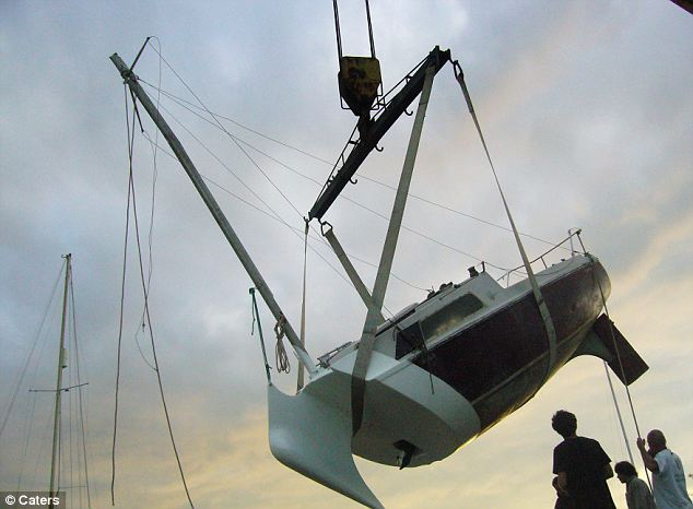 Down she goes: A crane lowers the strangely shaped vessel towards the water on a visit to Normandy