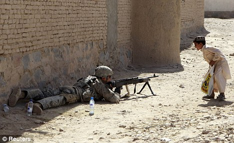 An Afghan boy greets a U.S. soldier manning a checkpoint outside Kandahar (file picture)