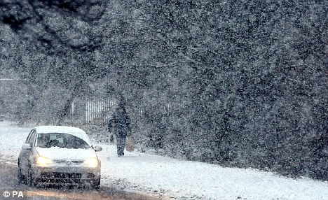 Chilly: A car drives carefully in a blizzard in North Tyneside, as the current cold spell continues to grip the country. Scientists say we are three times as likely to have cold winters in the future