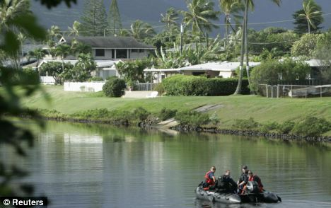 Tranquil: A Coast Guard patrol dingy rides up the canal near the house in Kailua where President Obama is staying