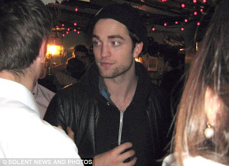 Good times: Robert Pattinson and Kristen Stewart chatted to friends and fans and were also seen singing as the New Year arrived