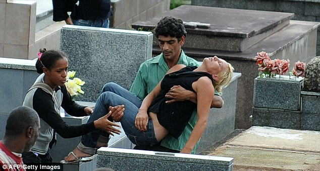 Too much to bear: A relative of one of the landslide victims collapsed during the burial at the the cemetery in Teresopolis