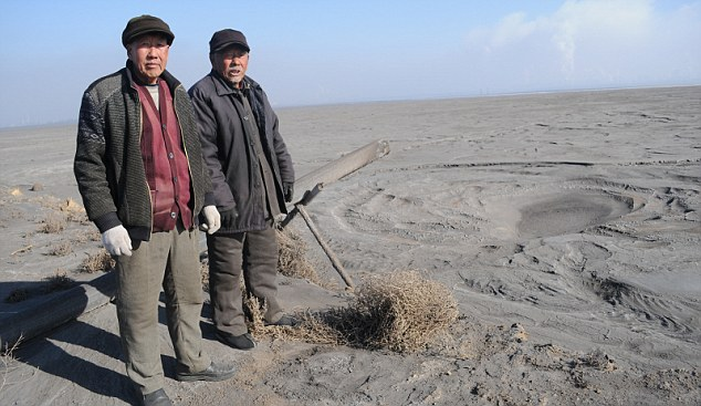 Villagers Su Bairen, 69, and Yan Man Jia Hong, 74, stand on the edge of the six-mile-wide toxic lake in Baotou, China that has devastated their farmland and ruined the health of the people in their community