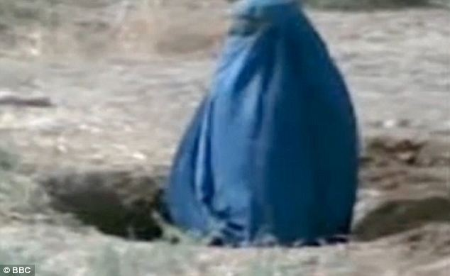 Barbaric: Video footage shows Siddqa, 25, covered completely by a blue burkha, buried up to her waist in the ground as a crowd of people watches on  Read more: http://www.dailymail.co.uk/news/article-1350945/Horrific-video-emerges-Taliban-fighters-stoning-couple-death-adultery