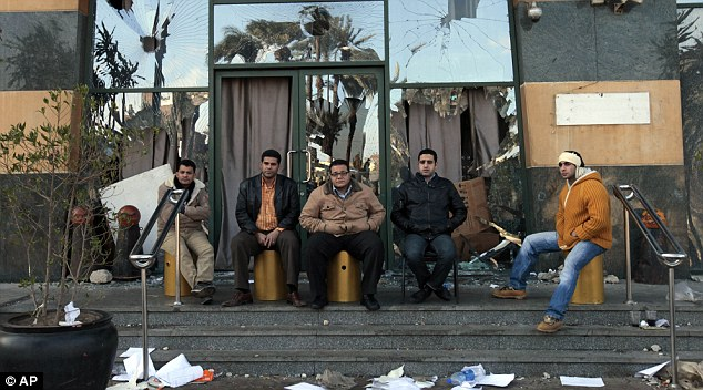 Egyptian men try to protect the Arcadia shopping centre from looting. It was already damaged and partially set on fire