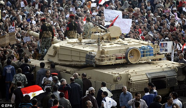 Show of strength: Egyptians surround an army tank during protests in central Cairo on the sixth day of action