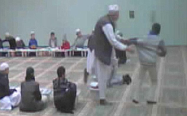 Grabbed: Secretly filmed footage from the Markazi Jamia mosque shows a teacher pulling a pupil towards him and striking him on the back
