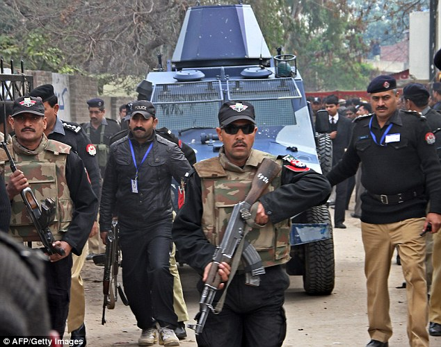Protection: A police escort guarding Davis as he was brought to a Lahore court on Friday