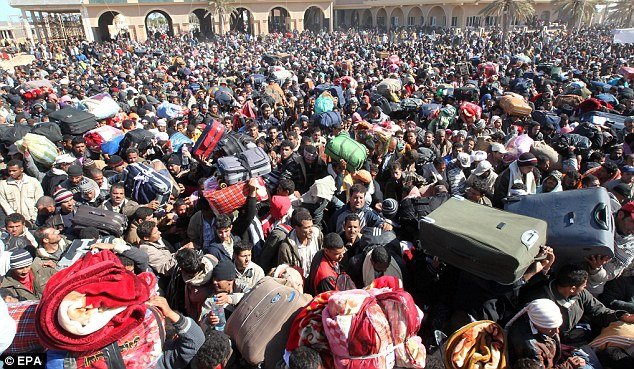 Desperate: Refugees fleeing the unrest queue up at the Libya-Tunisia border. The UN has warned that the situation 'is reaching crisis point'. Some 15,000 people are expected to cross the border today alone