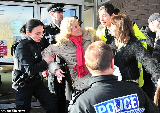Clash: Police pull away a protester after hundreds stormed Birkenhead county Court to make a citizens' arrest of the judge